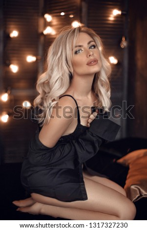 Sexy blonde woman portrait in black shirt and lingerie. Beautiful fashion blond girl model over bokeh lights dark background. Alluring female with makeup and curly hair style posing on bed.  #1317327230