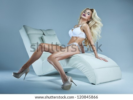 Sexy blonde woman with winter makeup sitting on a stylish leisure
