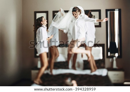 Sexy bride & bridesmaids jumping on bed before wedding