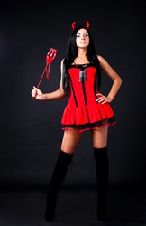 sexy brunette girl wearing a halloween costume of an imp