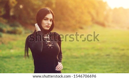 Sexy brunette girl wearing black dress outdoors. Women fashion and lifestyle. Sensual lips, beauty face portrait. Sexuality, sensuality and feminity concept