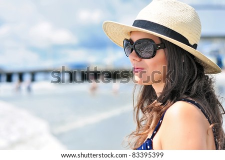 Sexy brunette girl with beach hat, summer dress and sunglasses staring in vain with the ocean reflection in her glasses