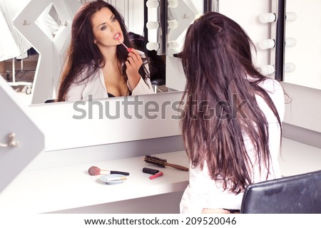 Sexy brunette in white shirt sitting on the visage\'s by the mirror putting makeup on