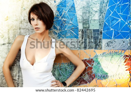 Sexy brunette lady in white shirt standing near a brick wall