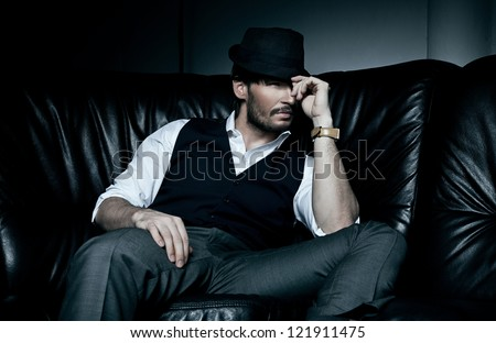 Sexy brunette man lies on the black couch