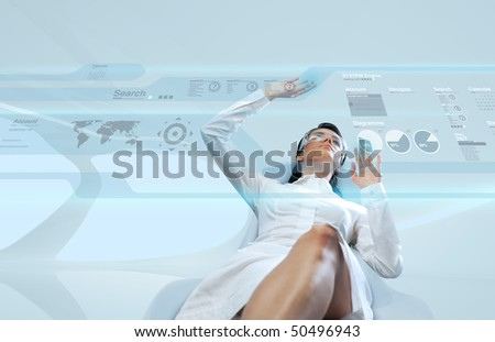 Sexy brunette wearing white suit logging into the system (Attractive young adults in futuristic interfaces / interiors series)