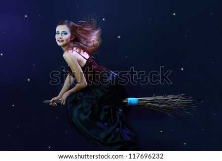 Sexy brunette witch flying on broom on a dark sky with stars
