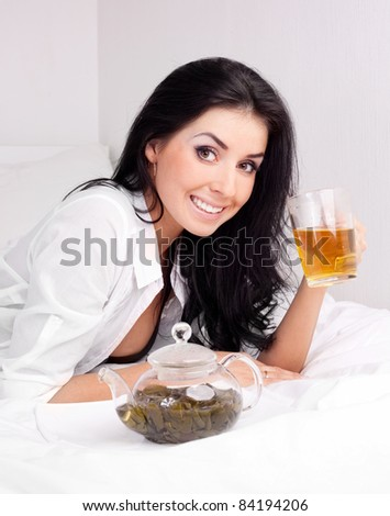 sexy brunette woman drinking green tea on the bed at home