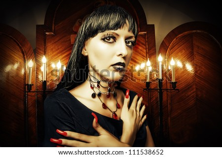 sexy brunette woman in a mystical room with candles in candlesticks