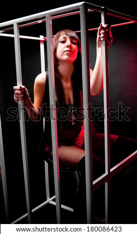 Sexy brunette woman in handcuffs sitting in cage from white grids