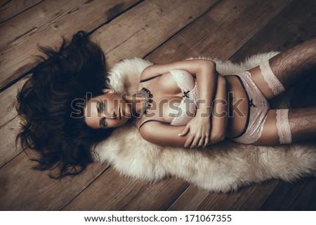 Sexy brunette woman lying on wooden floor