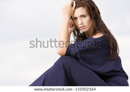 Sexy brunette woman posing in violet dress.