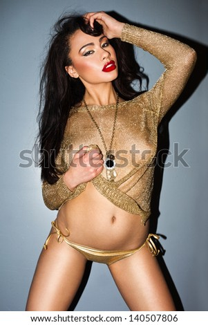 sexy brunette woman wearing gold lingerie on grey