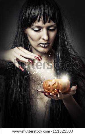Sexy brunette woman witch making magic to pumpkin