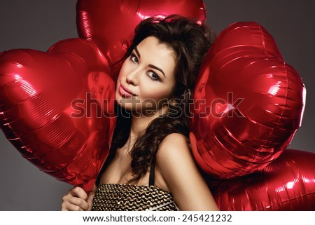 Stock Photo sexy brunette young woman in golden dress with a heart-shaped balloons. Valentine's day