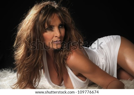 Sexy busty older woman in t-shirt looking away on floor