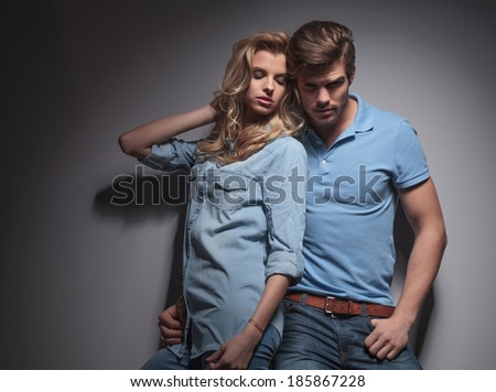 sexy casual couple , woman leaning against her boyfriend in studio