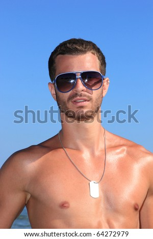sexy caucasian fit man posing at the  beach