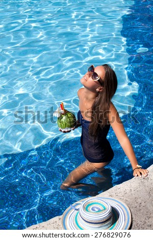 Sexy cheerful woman in bikini relaxing at the luxury poolside. Girl at travel spa resort pool. Summer luxury vacation.