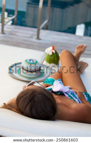 Sexy cheerful woman relaxing at the luxury poolside. Girl at travel spa resort pool in Hawaii island. Summer luxury vacation. (focus on woman head)
