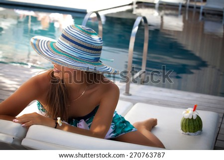 Sexy cheerful woman, relaxing at the luxury poolside. Girl at travel spa resort pool. Summer luxury vacation.