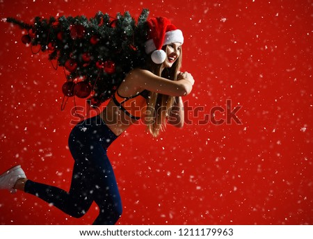 sexy Christmas fitness sport woman wearing santa hat holding  xmas tree on her shoulders. running forward on a snowing red background