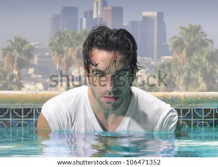 Sexy close-up portrait of a handsome man in glamorous swimming pool with city background