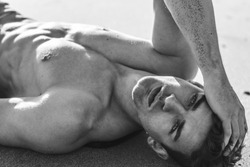 Sexy closeup portrait of handsome topless male model lying on the beach. Black and White.