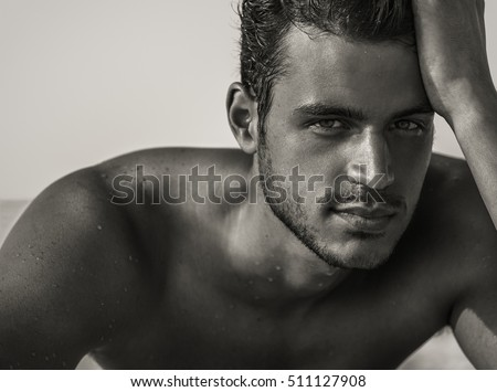 Sexy closeup portrait of handsome topless male model with beautiful eyes on the beach. Black and White.  #511127908