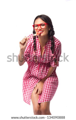 Sexy college student wearing geeky glasses and pigtails while biting a large lollipop, shot on white background