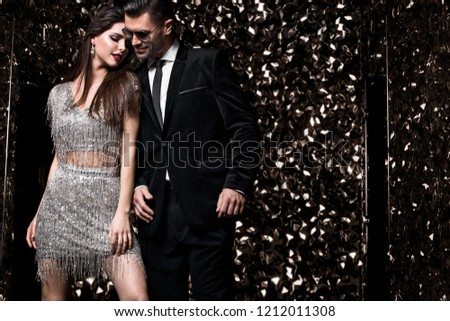 Sexy couple on shine background. Friends on celebrating, party. Hollywood stars.
