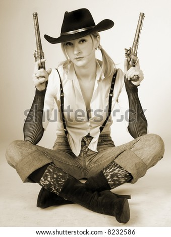 sexy cowgirl with old-fashioned gun - stock photo