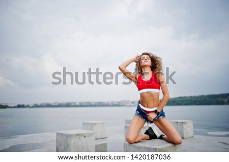 Sexy curly model girl in red top, jeans denim shorts and sneakers posed at stone cubes against cloudy sky and lake. #1420187036