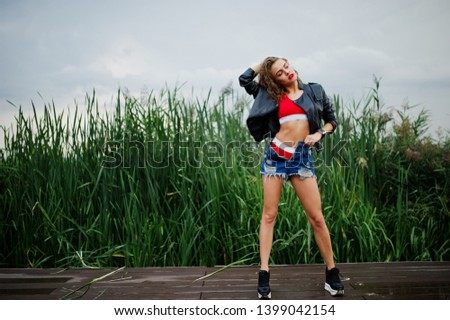 Sexy curly model girl in red top, jeans denim shorts, leather jacket and sneakers posed in the reed. #1399042154