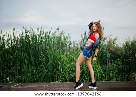 Sexy curly model girl in red top, jeans denim shorts, leather jacket and sneakers posed in the reed. #1399042166