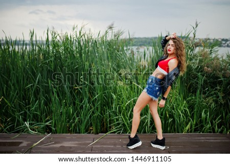 Sexy curly model girl in red top, jeans denim shorts, leather jacket and sneakers posed in the reed.