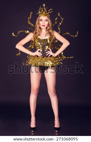 sexy disco party woman dressed in a unique golden costume with metal wings. Perfect for stylish club, disco and fashion events