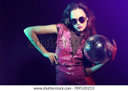 Sexy disco party woman. Sunglasses, sequin party dress, disco balls, neon lights, bright makeup.