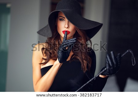 Sexy dominant woman in hat and whip showing no talk, bdsm