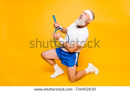 Sexy emotional cool pensioner grandpa practising rock music on a  sport equipment, stands on one knee, yell and shout. Body care, hobby, weight loss, lifestyle, strength and power, health