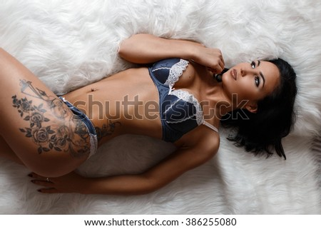 Stock Photo Sexy Europeans woman with tattoo in lingerie lying on the bed