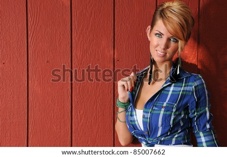 Sexy Farm Girl leaning against a red barn