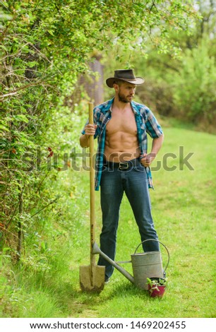 sexy farmer hold shovel and watering can. muscular ranch man in cowboy hat. happy earth day. Eco living. farming and agriculture cultivation. Garden equipment. Eco farm. Harvest. Warn atmosphere.
