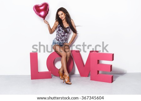 Sexy fashion blonde woman posing in jeans shorts and bodysuit. Studio photo on pink background, standing next to love sign. Valentines day, heart shaped balloon