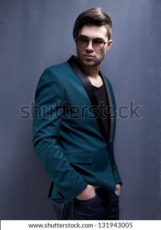 sexy fashion male model dressed elegant - casual posing against wall