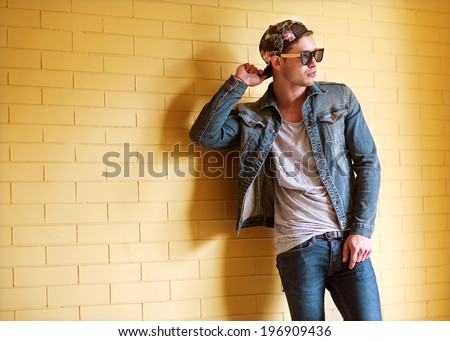 sexy fashion man with beard dressed casual smiling brick wall
