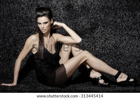 Stock Photo sexy fashion model with natural brunette hair, long legs, full lips, perfect skin, wearing black shoes and transparent cocktail dress, sitting on black carpet, beauty photoshoot, retouched image