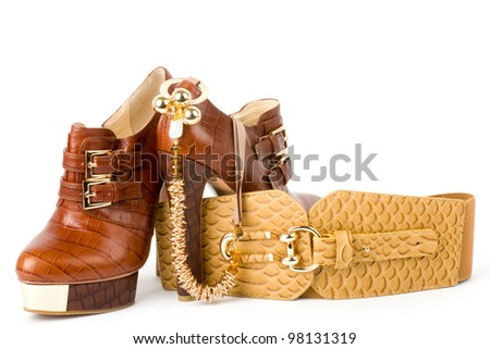 Sexy fashionable shoes, golden jewelry and strap isolated on white background.