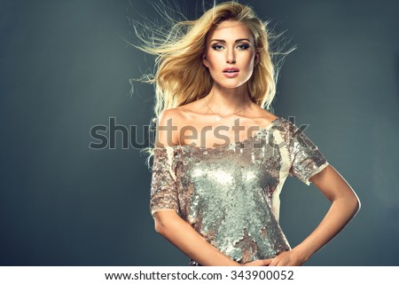 Sexy fashionable woman in glitter dress and nice hair style. Studio photo