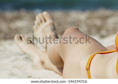 Sexy feet with anklet. Woman relaxing on the beach
